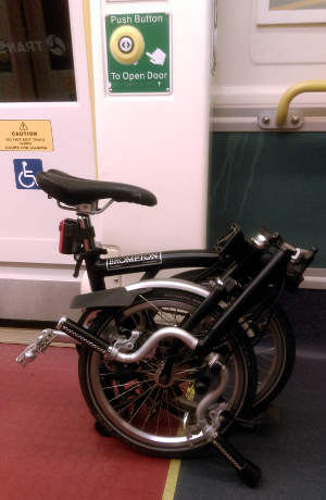 Folded Brompton on Queensland Railways train